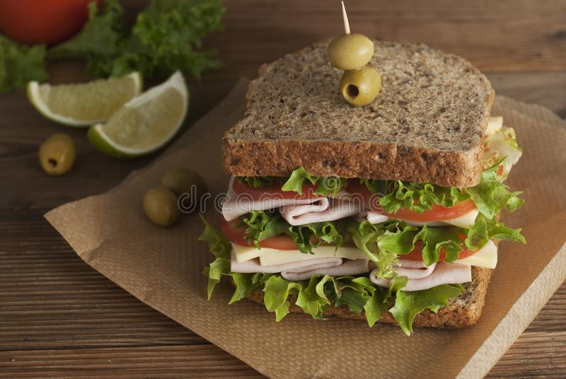 Double sandwich with ham, cheese, lettuce, tomato and green olives. Whole grain bread. Snack or take away food. Black background. Isolated stock photo
