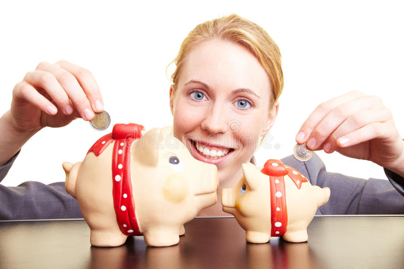 Double savings. Businesswoman dropping coins in two piggy banks royalty free stock images
