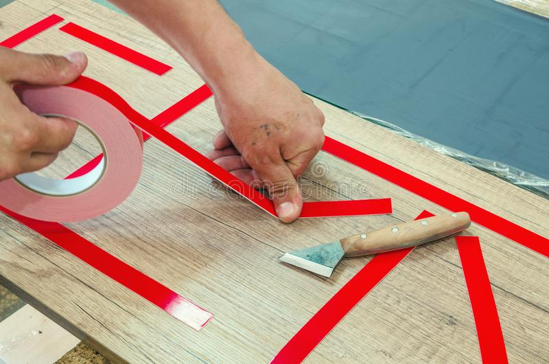 Double-sided tape, the master prepares the part for further sticking the mirror. Close-up stock photography