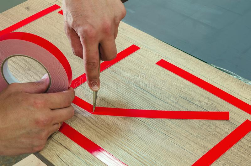 Double-sided tape, the master prepares the part for further sticking the mirror. Close-up royalty free stock photography