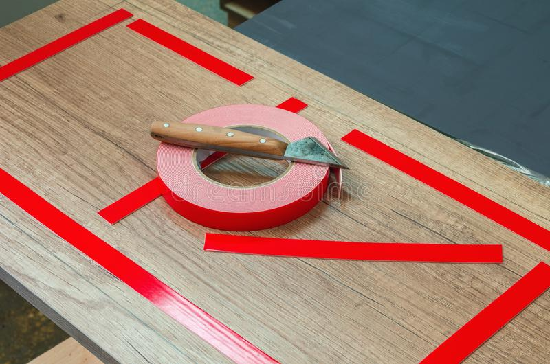 Double-sided tape, the master prepares the part for further sticking the mirror. Close-up royalty free stock photo