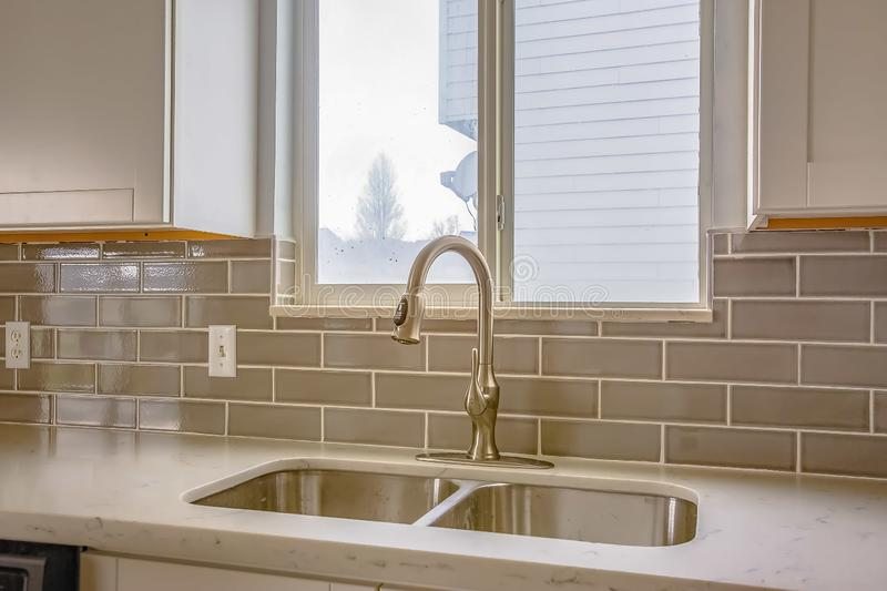 Double sink and faucet of a kitchen with view of outdoors through the window stock photos