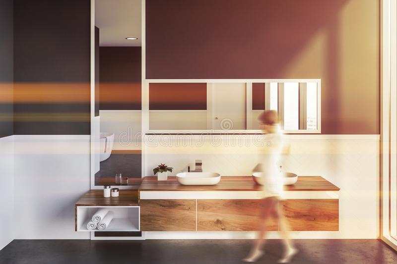 Double sink in gray bathroom, woman. Woman in interior of modern bathroom with white and gray walls, concrete floor, double sink standing on wooden countertop stock photography