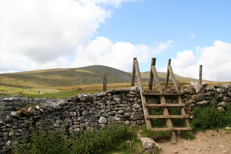 Double Stile. A double stile for walkers over a dry stone wall on the slopes of Ingleborough in the Yorkshire Dales National Park stock photos