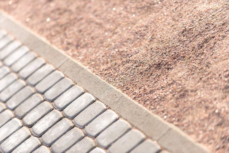 Double texture de sable et de tuiles routières Le concept de chemins de jardin et de ville, le design soigné du jardin et des env photographie stock