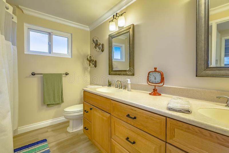 Double vanity with wooden cabinets inside a bathroom with small window stock images