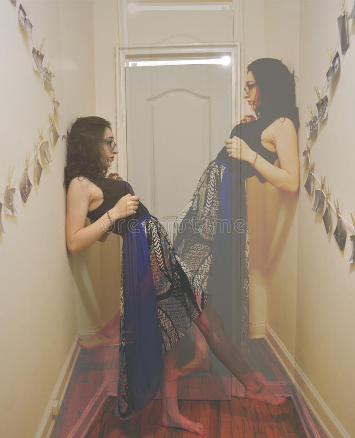 Double vision. Double exposed mirror image portrait of a young woman royalty free stock images