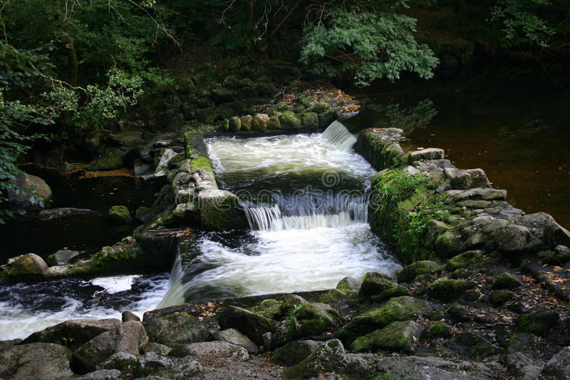 Weirs on river. Double weir on a river of two linked pools and water flowing between them. Surrounded by rocks and trees royalty free stock photos