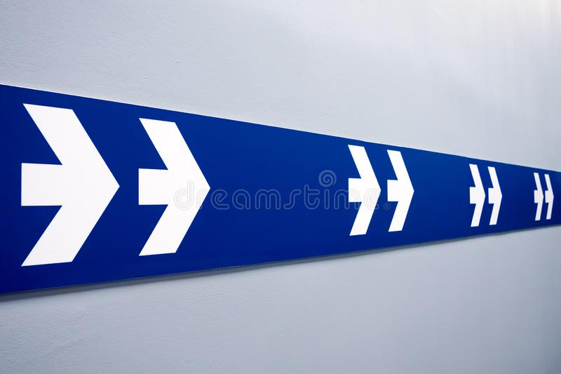 Double white arrows sign on blue strip pointing to exit stock photo