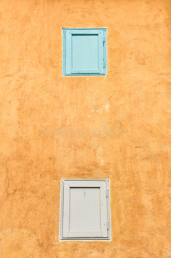 Double Windows On Yellow Wall Royalty Free Stock Image