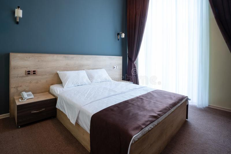 Double wooden bed, with white pillows, bedside tables on the sides, against the blue wall with lamps. stock images