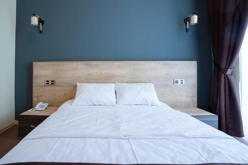 Double wooden bed, with white pillows, bedside tables on the sides, against the blue wall with lamps. royalty free stock photography