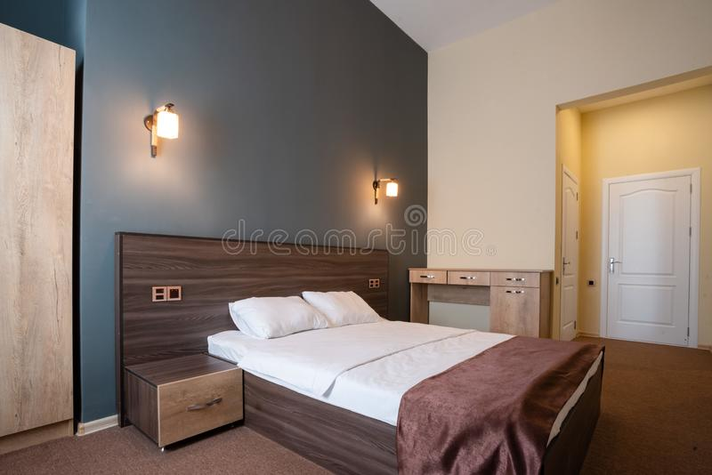 Double wooden bed, with white pillows, two bedside tables on the sides, against the blue wall with lamps. stock images