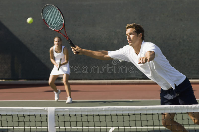 Doubles Player Hitting Tennis ball With Forehand. View of doubles player hitting tennis ball with forehand near net on court stock photo