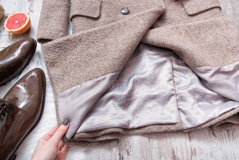 Doublure d'un manteau de laine dans une main du ` s de femme concept à la mode image libre de droits