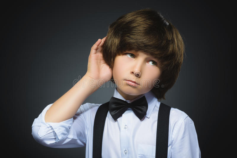Doubt, expression and people concept - boy thinking over gray background.  stock image