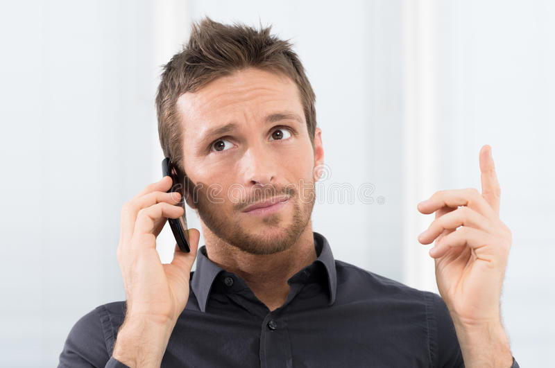 Doubt at phone. Businessman Listening Seriously On Mobile Phone In Office royalty free stock photo
