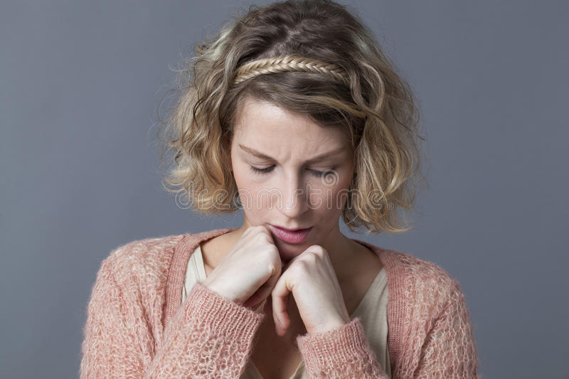 Doubt and worry concept for unhappy 20s woman. Doubt and worry concept - unhappy 20s woman with blond curly hair looking concerned with both fists hiding her royalty free stock photo