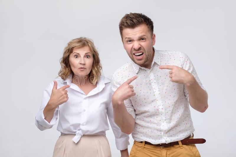 Woman and man asking who me, being upset questioning pointing fingers at themself stock image
