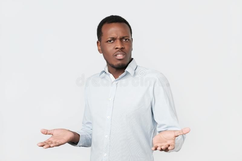Doubtful african man shrugs shoulders with confusion stock photo