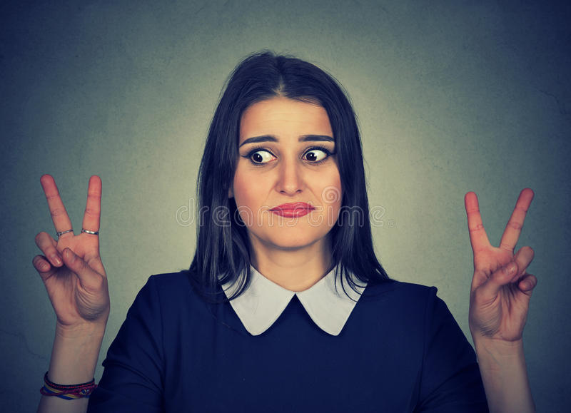 Doubtful confused woman with victory sign royalty free stock photos