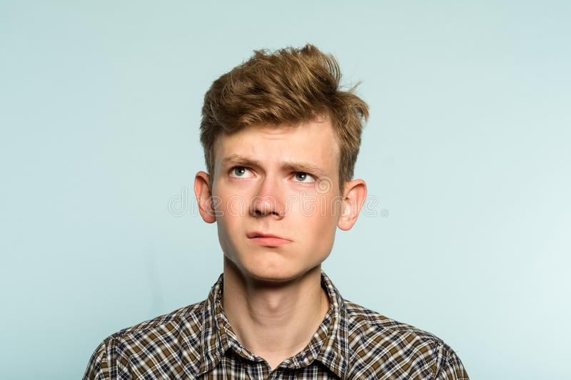 Doubtful dubious hesitant man expression look up. Doubtful dubious uncertain hesitant man looking up thinking over smth. portrait of a young guy on light royalty free stock photos