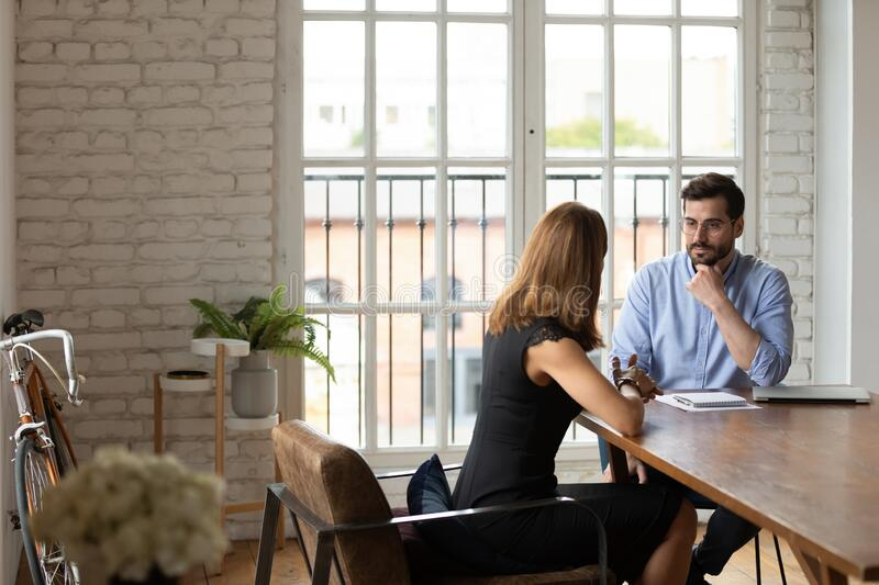 Doubtful hr manager listening to job applicant at interview royalty free stock photography