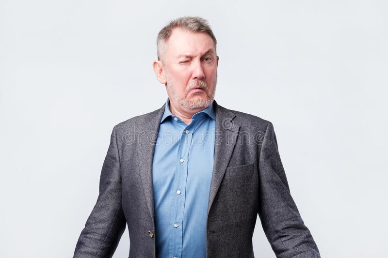 Doubtful senior man in jacket is confused royalty free stock photography