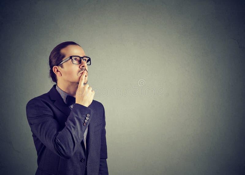 Doubtful serious man looking up in wonders royalty free stock image