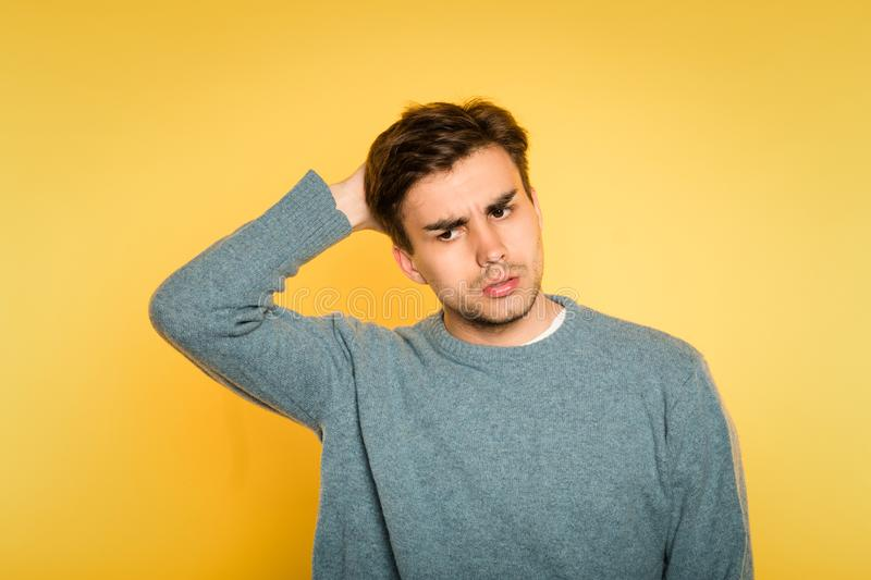 Doubtful uncertain hesitant man scratch expression. Doubtful dubious uncertain hesitant man scratching head. portrait of a young handsome brunet guy on yellow royalty free stock photography