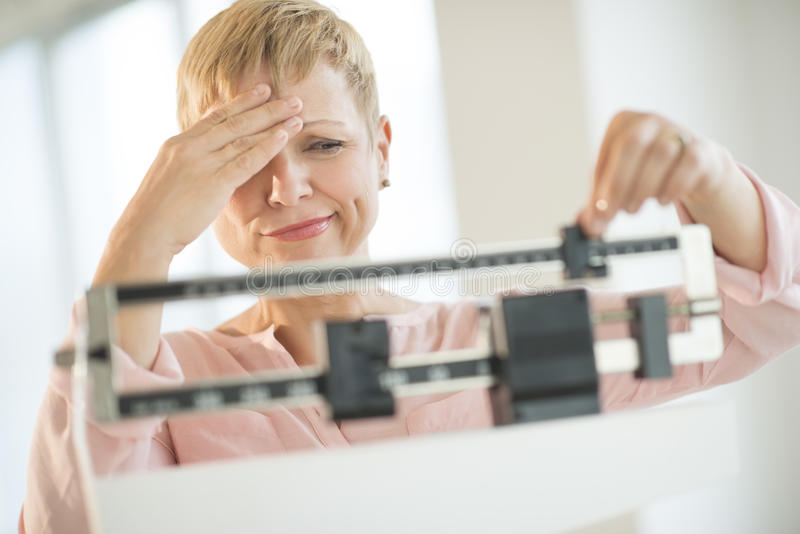Doubtful Woman Adjusting Weight Scale royalty free stock images