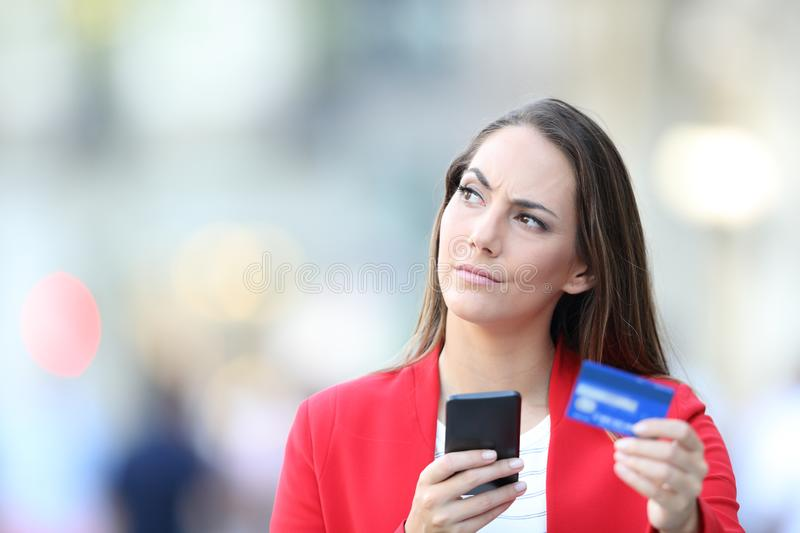 Doubtful woman holding credit card and cell phone stock image