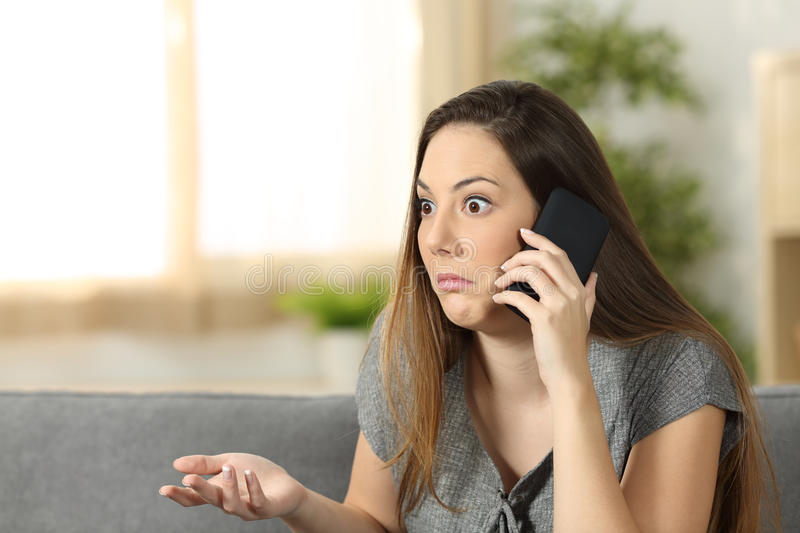 Doubtful woman listening a phone call royalty free stock photography