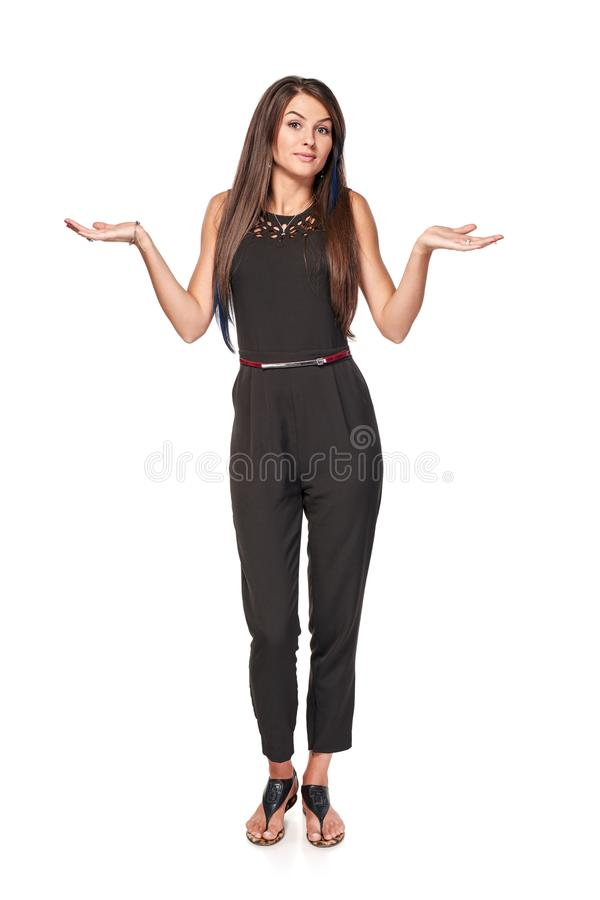 Doubtful woman shrugging shoulders. Doubtful woman standing in full length with two opened hand palms shrugging shoulders, isolated on white background royalty free stock image