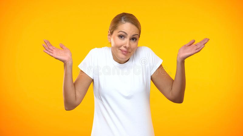 Doubtful woman throwing up hands on bright background, having no idea, choice royalty free stock images