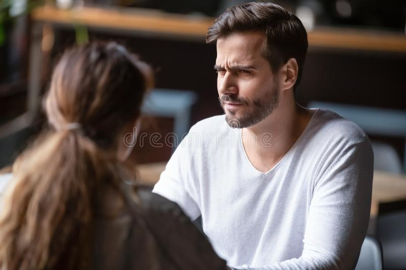 Doubting dissatisfied man looking at woman, bad first date concept. Doubting dissatisfied men looking at woman, bad first date concept, young couple sitting at royalty free stock photography
