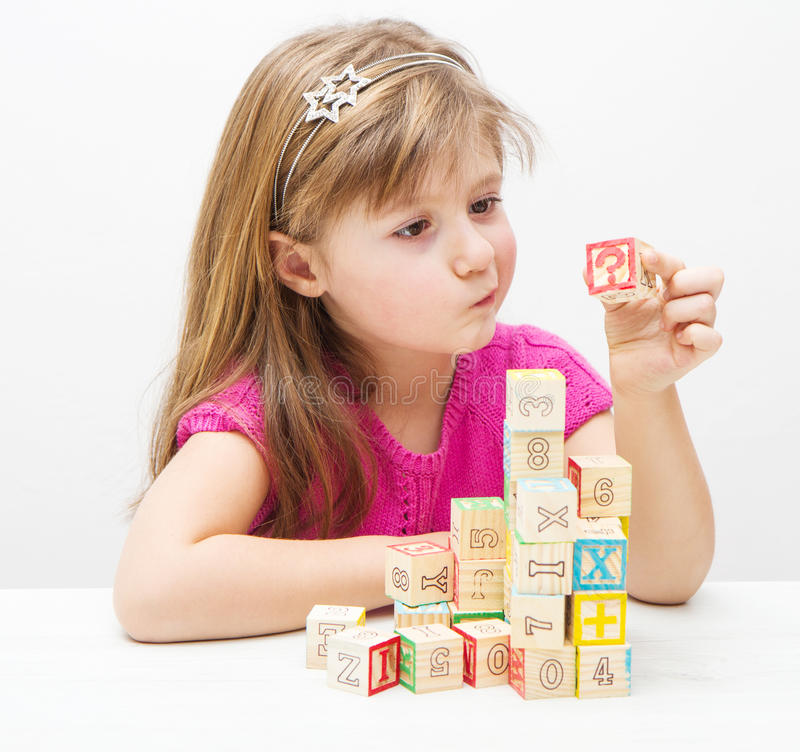 A doubting girl playing with wooden cubes royalty free stock photo