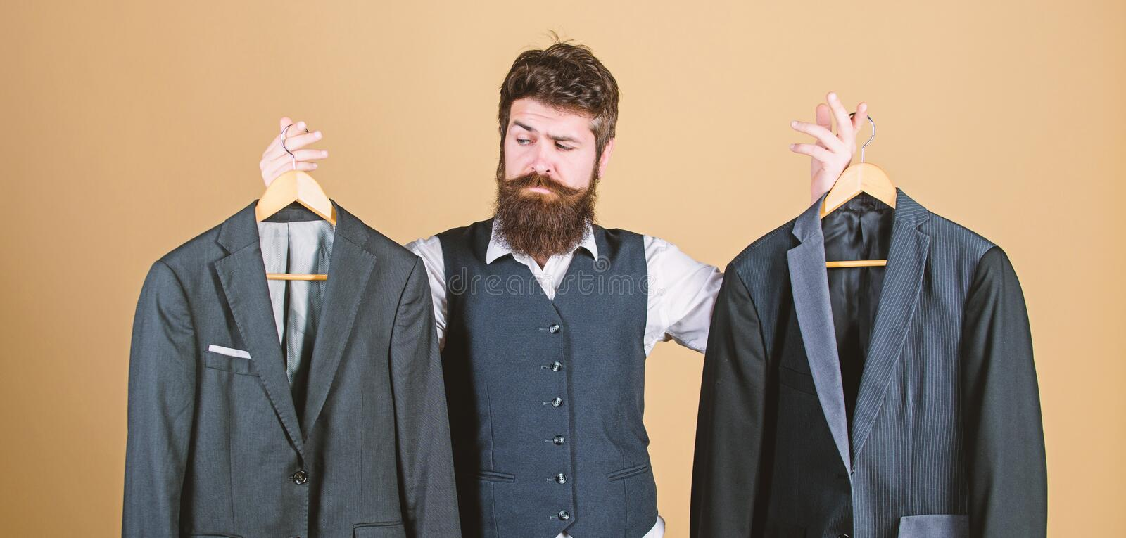 Doubting about his choice. Bearded man holding suit jackets in store, choice concept. Hipster making shopping choice in. Shop. Businessman choosing which formal royalty free stock image