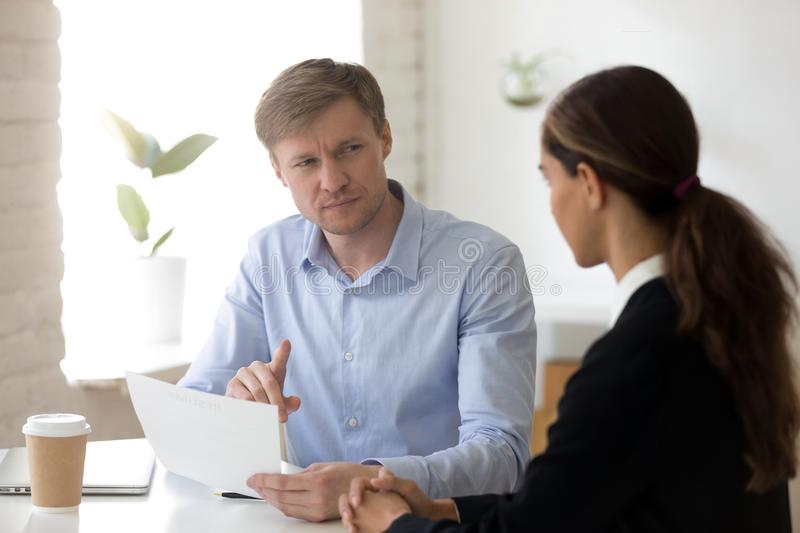 Doubting hr manager looking with suspicion at applicant. Doubting hr manager having questions for applicant at job interview, recruiter read bad resume, looking stock images