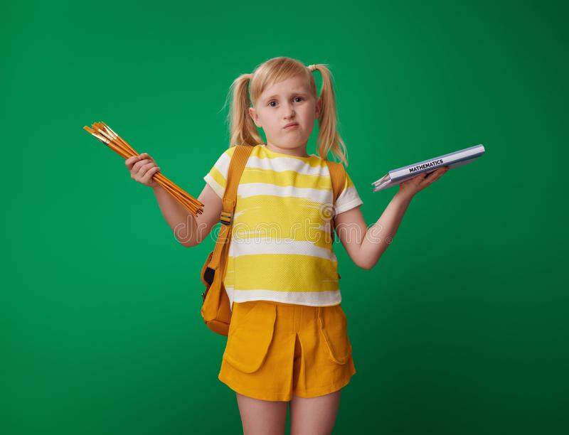 School girl choosing between sciences and art isolated on green royalty free stock photography