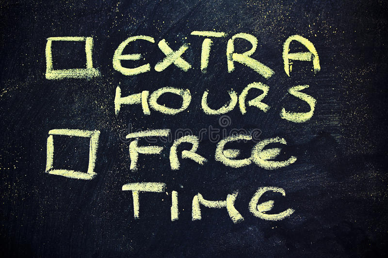 Doubts: choice between work and free time. Chalk writings on blackboard, choice between extra working hours and free time stock photos