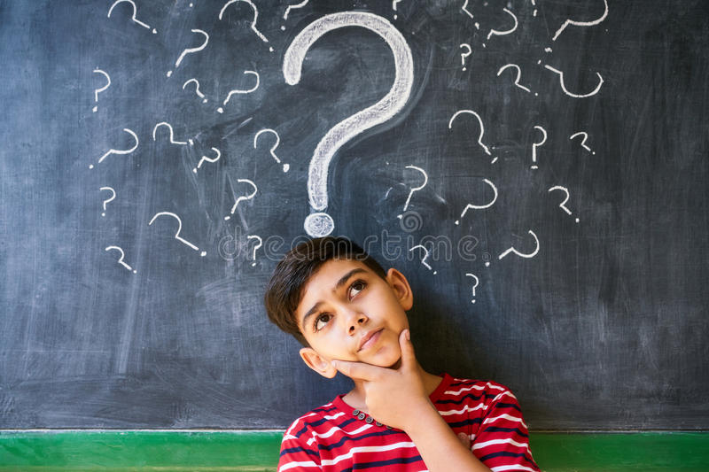 Doubts And Question Marks With Child Thinking At School. Concepts on blackboard at school. Hispanic boy with doubts and thoughts in class. Portrait of male child royalty free stock photography