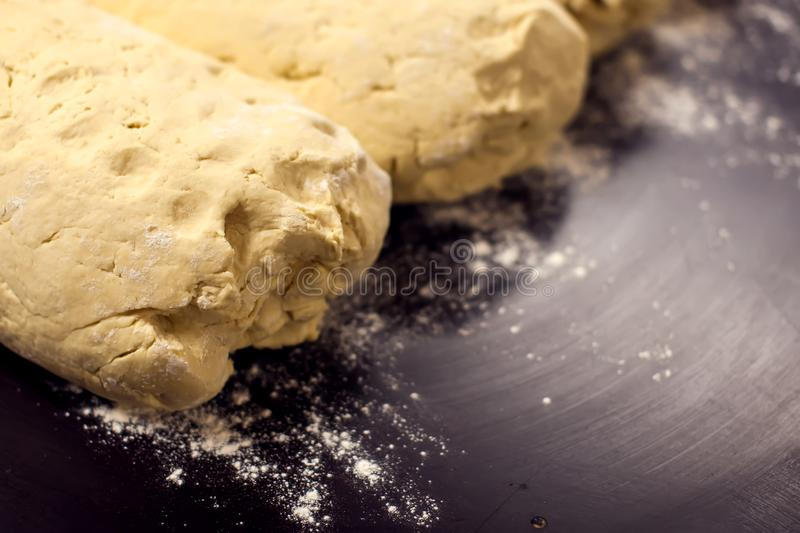 A dough with flour on the black background. Homemade food concept stock photo