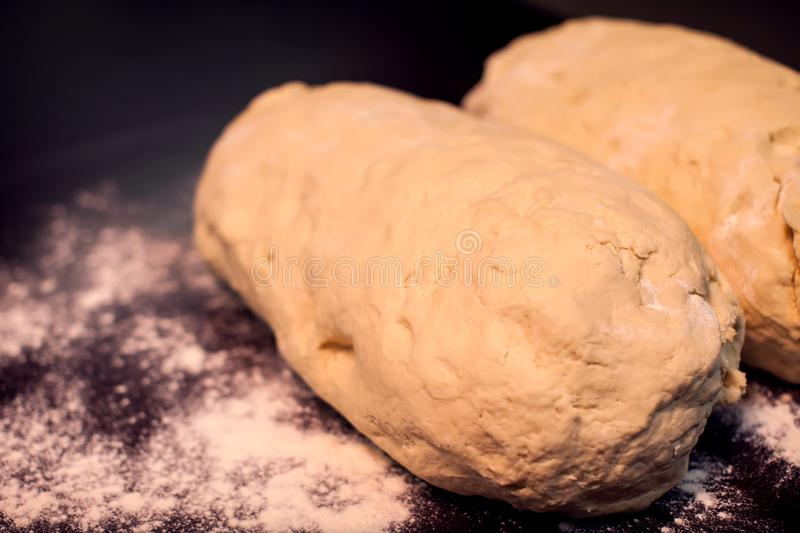 A dough with flour on the black background. Homemade food concept royalty free stock images