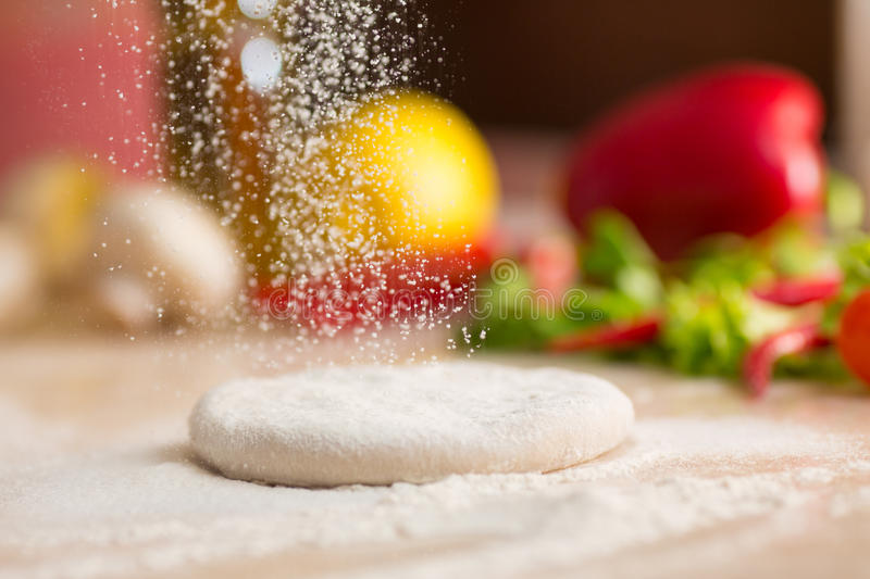 Dough for Italian pizza preparation. Falling flour royalty free stock images