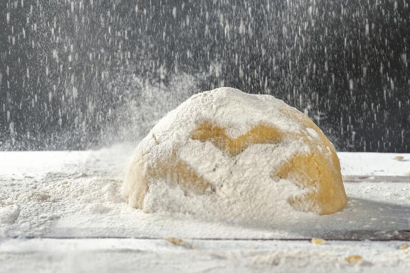 Dough for the manufacture of confectionery with flour on flour, concept royalty free stock photo