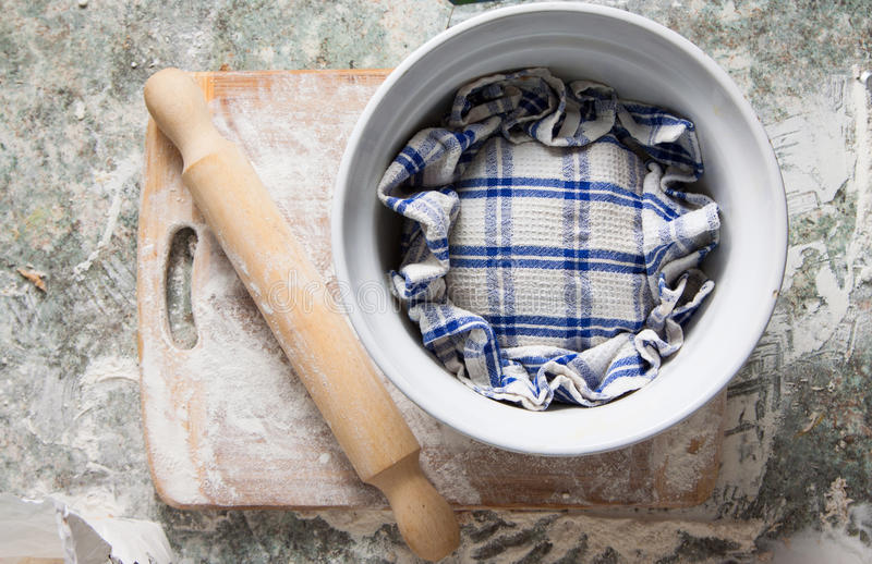 Dough rising covered with towel stock photography