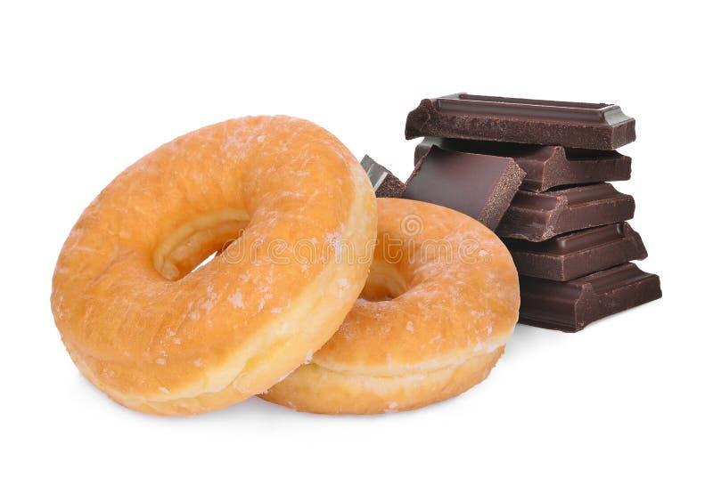 Doughnut και σκοτεινοί φραγμοί σοκολάτας που απομονώνονται σε ένα λευκό στοκ φωτογραφία