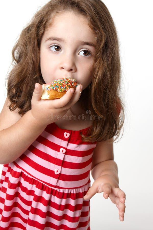 doughnut που τρώει το κορίτσι ε&lambd στοκ φωτογραφία