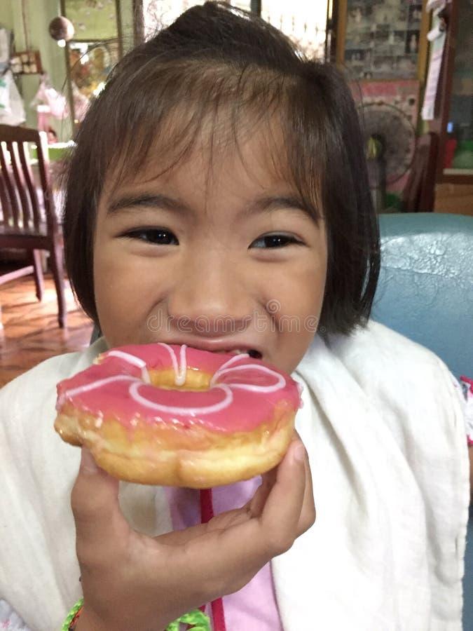 doughnut που τρώει το κορίτσι ε&lambd στοκ εικόνες με δικαίωμα ελεύθερης χρήσης